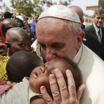 Pope Francis kisses a baby as he visits a refugee camp, in Bangui, Central African Republic, Sunday, Nov. 29, 2015. The Pope has landed in the capital of Central African Republic, his final stop in Africa and where he will seek to heal a country wracked by conflict between Muslims and Christians. (AP Photo/Andrew Medichini)